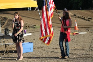 Rebekah Schoenfelt, left, sings the National Anthem while Makayla Livingston, right, holds the American Flag prior to the start of the Motocross Races on Tuesday night.